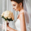 Vertical portrait of beautiful young bride holding roses wedding bouquet at white curtain background. — Stockfoto #78536152