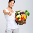 Happy woman holding basket of raw vegetables — Stock Photo #64038291