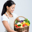 Attractive woman holding a basket of vegetables — Stock Photo #64038347