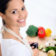 Smiling woman slicing vegetables in a kitchen — Stock Photo #64038537