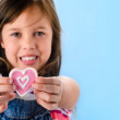 Girl holds out a pink heart shape cookie — Stock Photo #65455105