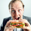 Funny business man eating sandwich — Stock Photo #65455435