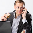Multi tasking businessman eats and works — Stock Photo #65455983