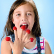 Young child eating raspberries — Stock Photo #65459339