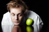 Businessman looking at bright green apple — Stockfoto