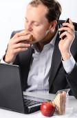 Hardworking man eating at his desk — Stock Photo