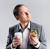 Businessman eating  sandwich on the go — Stock Photo