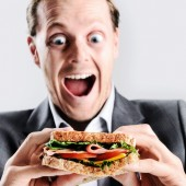 Comical man eating sandwich — Stock Photo