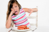 Girl sits at table unhappy with food — Stock Photo