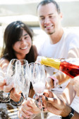 Smiling friends celebrating a special occasion with drinks — Stock Photo