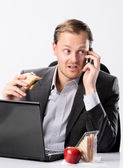 Multi tasking businessman eats and works  — Stock Photo