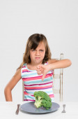 Frowning upset girl with her vegetables  — Stock Photo