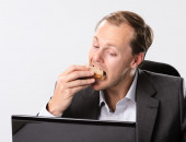Businessman eats and works — Stock Photo