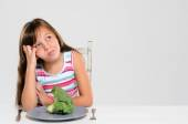 Kid unhappy with her vegetables  — Stock Photo