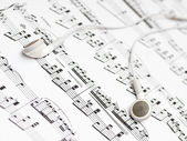 一副耳机躺在工作表上,音乐记谱法 — 图库照片