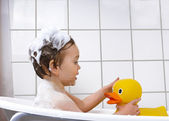 Cute toddler playing in a bathtub — Stock Photo