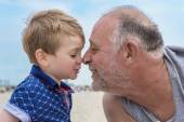 Grandfather and grandson on the beach — Stock Photo