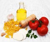 Olive oil, mozzarella cheese, fusilli pasta, garlic and tomatoes — Stock Photo