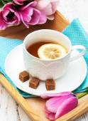 Cup of tea and pink tulips — Stock Photo