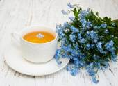 Cup of teand forget me not flowers — Stock Photo