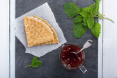 Pancake with jam and sprig of mint. — Stock Photo