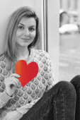 Smiling young woman holds red heart in her hands — Stock Photo