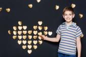 Smiling boy assembling  golden heart on dark background — Stock Photo