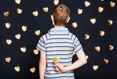 Boy holding gold heart behind his back — Stock Photo