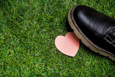 Heart lying on the grass tramled by big black boots — Stock Photo