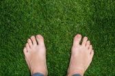 Mens feet standing on grass close up — Stok fotoğraf