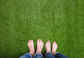 Men and woman  legs standing together on grass — Stock Photo