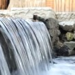 Artificial waterfall in a pond with stone — Stock Video #80557098