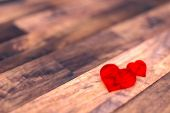 Red glass heart isolated on wooden floor — Stock Photo