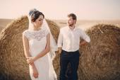 Happy wedding couple in a field — Stock Photo