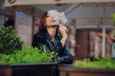 Beautiful glamorous brunette smoke electronic cigarette — Stock Photo