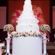 A multi level white wedding cake on a silver base and pink flowe — Stock Photo #64972013