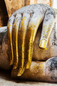 Gold leaf offerings on slender fingers of wat si chums iconic bi — Stock Photo