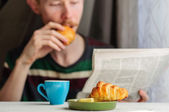 Breakfast with coffee and croissant with young man on backgroung — Stock Photo