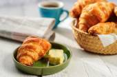 Breakfast with fresh baked croissants, butter and coffee, newspaper — Stock Photo