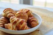 Čerstvé croissanty na pečící papír — Stock fotografie
