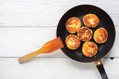 Cottage cheese pancakes in frying pan on wooden background — Stock Photo