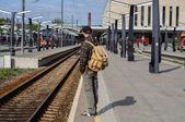 Jovem aguarda o trem na estação ferroviária — Fotografia Stock