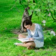Young woman reads a book under blooming tree — Stock Photo #74840231