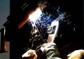 сварщик рабочего сварит металлическую структуру на темном фоне — Стоковое фото