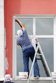 Woman paints the window frame standing on the ladder — Stok fotoğraf