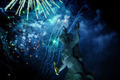 Breaks fireworks over the ancient sculpture.at night in the dark sky — Stockfoto