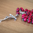Red rosary beads with crucifix — Stock Photo #70214981
