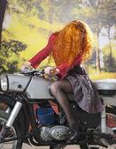 Redhad girl on motorbike — Stock Photo