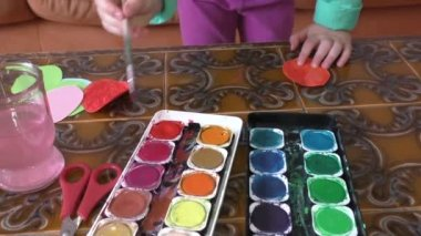 Little girl painting watercolors with her hands — Stock Video