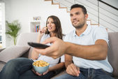 Young couple with popcorn watching movie at home — Stock Photo